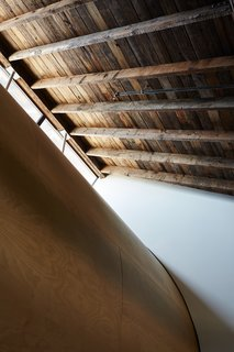 A giant plywood scoop curves down from a row of clerestory windows, refracting light.
