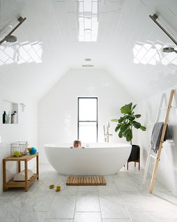 "The third floor houses the master suite and an 80-square-foot wet room. Existing walls were moved in to create a higher ""pinch point"" in the gable. Linear drains along the room's glass partition (not shown) capture the flow from twin Hansgrohe showerheads. The tub is by Victoria + Albert; the floor, wall, and ceiling tiles are from Arizona Tile."