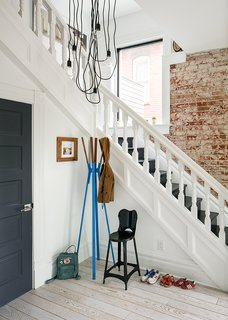 """Architect Caroline Wilding, then of Denver-based Design Platform, led the renovation. The staircase needed some treads replaced, but """"was left as original as possible,"""" she says. Wilding created the chandelier using wires from Color Cord and brackets from Home Depot."""