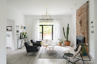 In the living room, layers of plaster were removed to expose the original brick fireplace surround, and a brick step was added; the black metal gas insert is by Heat & Glo. Tablo Tables from Normann Copenhagen sit on a rug from Safavieh, and the light fixture was designed and fabricated by Nathan Warner of Warbach.