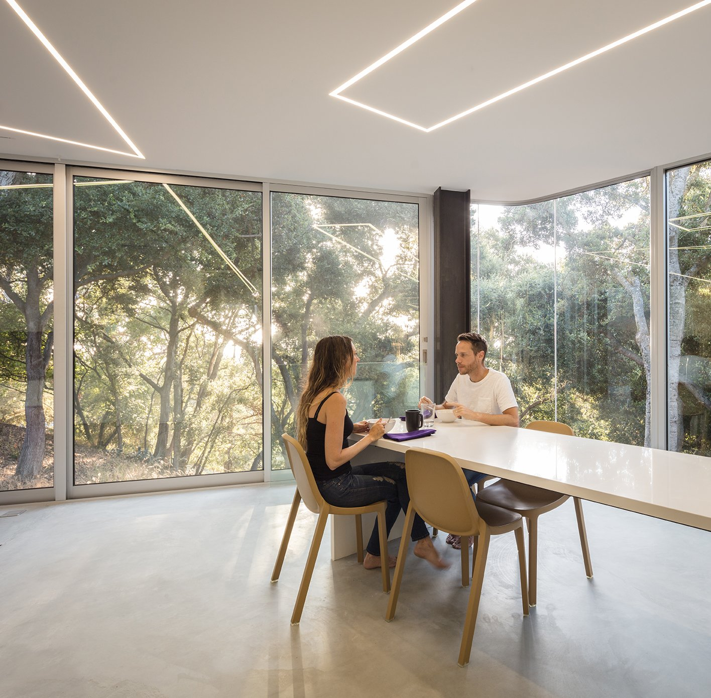Dining Room, Table, Chair, Concrete Floor, and Ceiling Lighting A 22-foot-long white composite quartz countertop provides both kitchen work space and a dining table. - Cupertino, California Dwell Magazine : September / October 2017  Photo 5 of 10 in The Conversation Pit Makes a Much-Appreciated Comeback at an Ultramodern Home in Cupertino