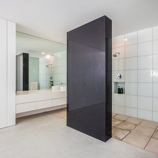 The master suite features a monolithic wall of quartz to separate the shower from the rest of the room.