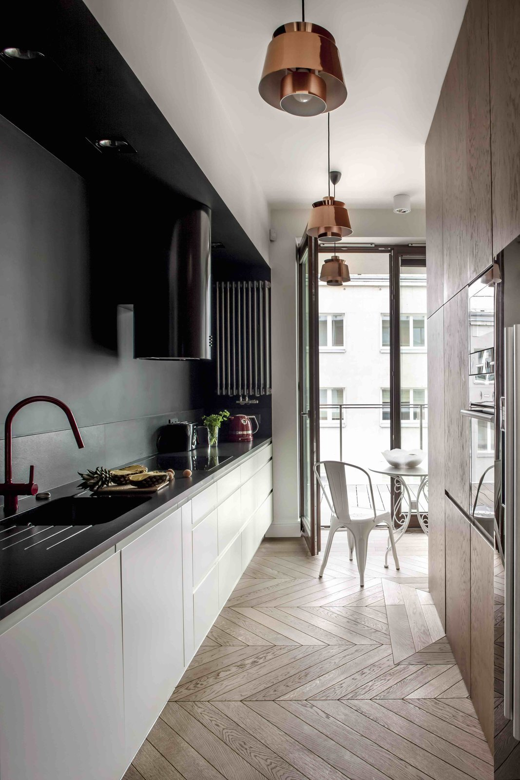 Kitchen, Wood Cabinet, White Cabinet, Light Hardwood Floor, Pendant Lighting, Recessed Lighting, Drop In Sink, Range Hood, and Range  Photo 2 of 12 in Filled With Color and Pattern, This Eclectic Apartment Brings a Little Madrid to Warsaw