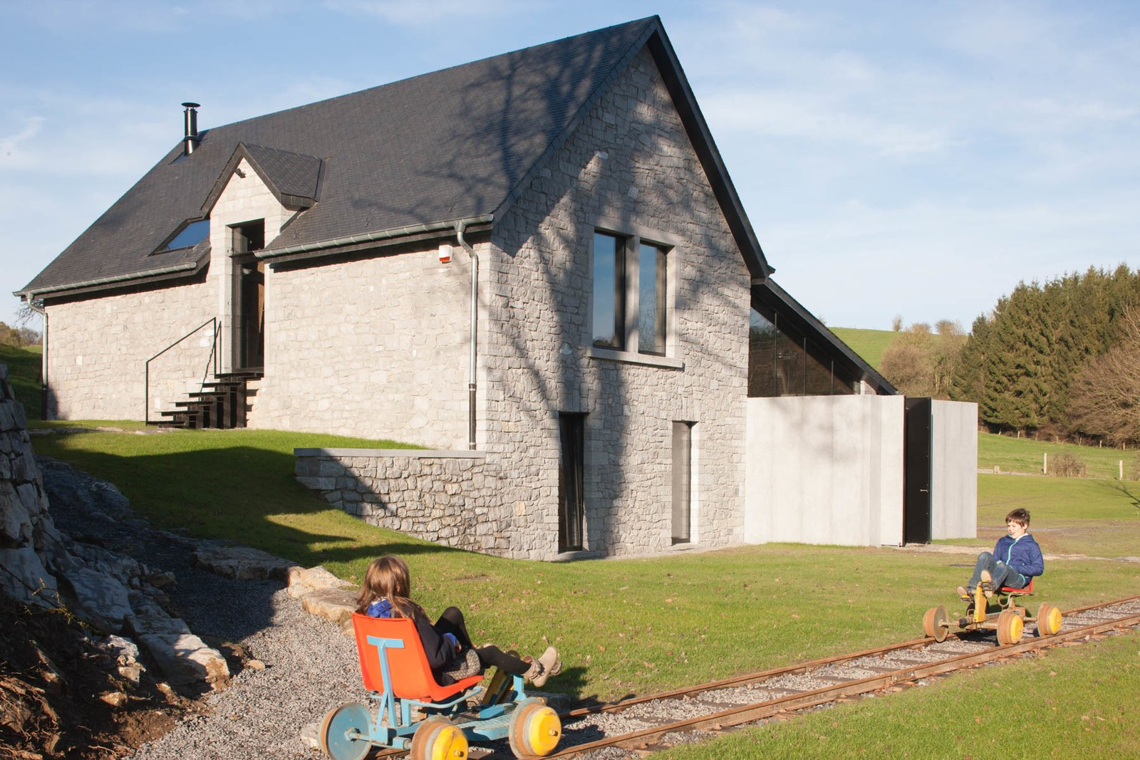 Exterior, Tile Roof Material, Stone Siding Material, House Building Type, Glass Siding Material, Gable RoofLine, Concrete Siding Material, and Cabin Building Type  Photo 3 of 16 in Stay at an Old Converted Train Station in the Belgian Countryside