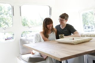 Kate Oliver and Ellen Prasse enjoy a cup of coffee inside their first client project: a 1976 Airstream Sovereign.