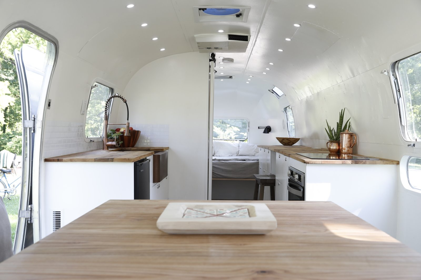 Kitchen, Wood Counter, White Cabinet, Drop In Sink, Cooktops, Dishwasher, and Subway Tile Backsplashe  Photo 8 of 15 in Airstream Dream Team: These Women Travel the Country, Turning Retro RVs Into Homes