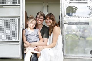 Ellen Prasse, Kate Oliver, and their daughter, Adelaide, in the doorway of a renovated Airstream.