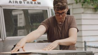 Ellen Prasse works with a table saw outside the Airstream she and Oliver are renovating.