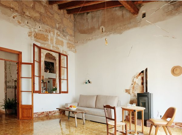 Living Room, Chair, Coffee Tables, Table, and Pendant Lighting  Photo 1 of 13 in A Salvaged Apartment on Mallorca Leaves its Roots Exposed