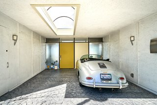 A skylit carport is finished with original hardware, graphic paving, and a painted door.