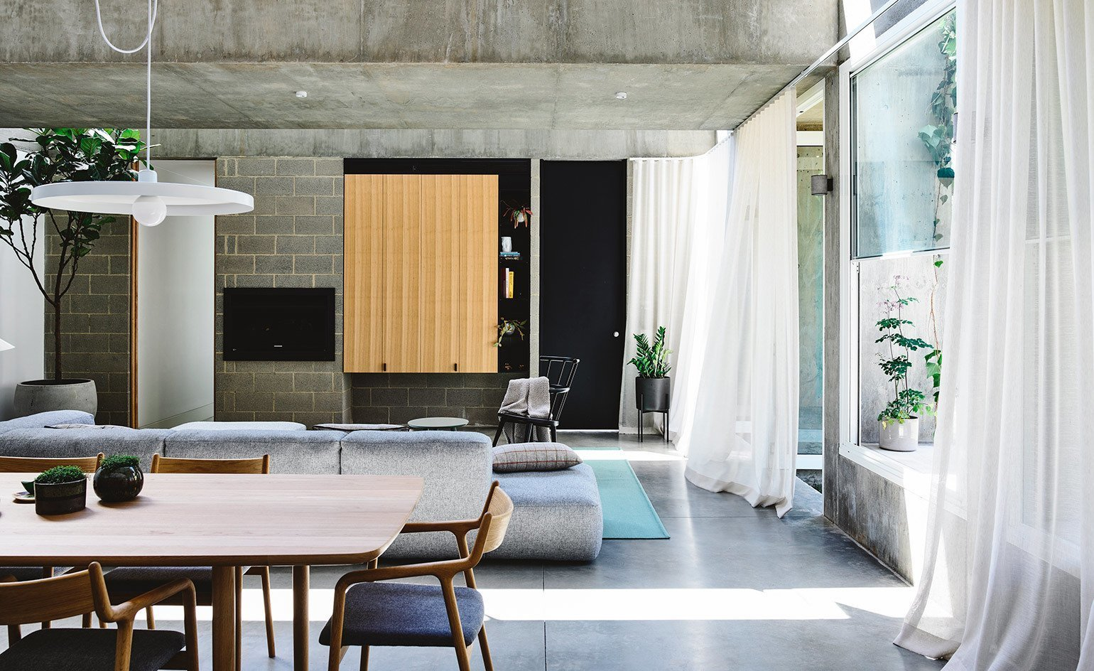 Living Room, Chair, Sofa, Coffee Tables, Table, Pendant Lighting, Accent Lighting, and Concrete Floor  Photo 3 of 11 in Vaulted Skylights and Concrete Columns Connect This Melbourne Home With the Sun