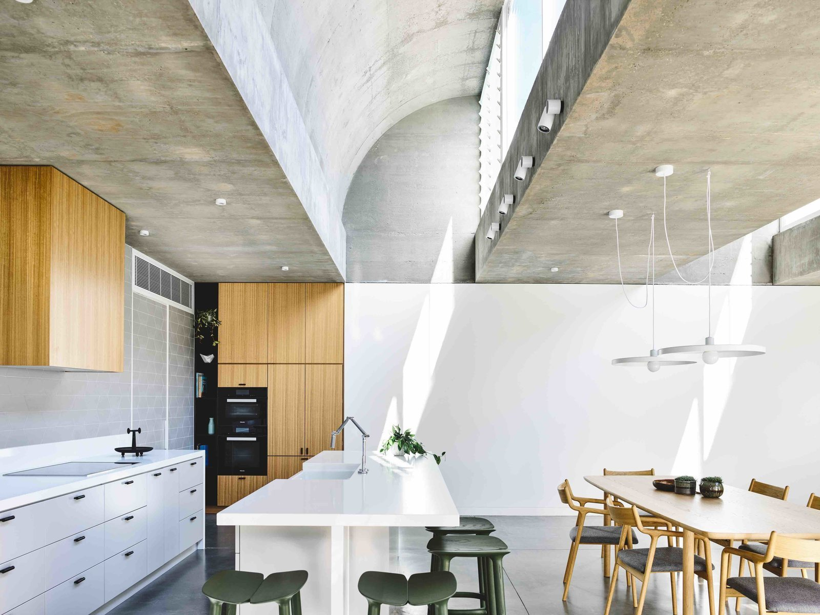 Kitchen, Wood Cabinet, Concrete Floor, Ceramic Tile Backsplashe, Pendant Lighting, Ceiling Lighting, Wall Oven, and Drop In Sink  Photo 4 of 11 in Vaulted Skylights and Concrete Columns Connect This Melbourne Home With the Sun
