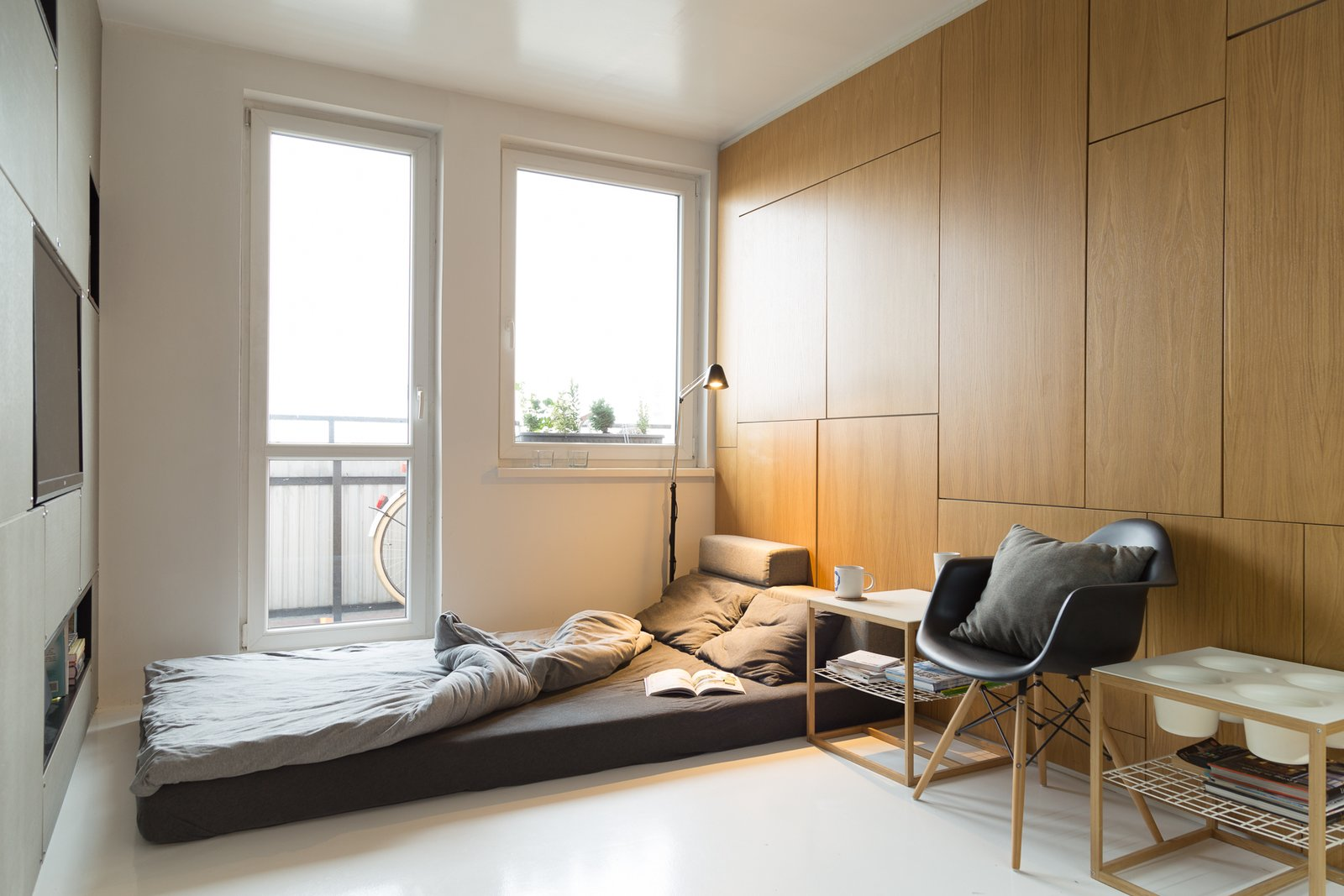 Bedroom, Bed, Night Stands, Chair, Storage, and Floor Lighting  Photo 3 of 8 in A Tiny Apartment in Slovakia Makes Clever Use of Space