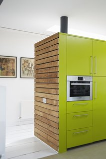 The sides of the cabinets are clad in sweet chestnut; their faces are painted a custom shade of green by Dulux.