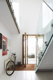 Glass panels on the staircase and second floor help spread light throughout the house.