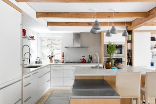 The kitchen's tubular lights were replaced with Heavy Medium pendants by Benjamin Hubert. The space is outfitted with a suite of Monogram cooking appliances.