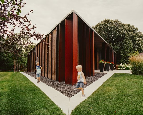 Owners Rachel and Nolan Ploegman's sons, Alex and Logan, run along the perimeter of their Parallelogram House in Winnipeg, Manitoba. Its raw shell and stretched geometry were conceived by 5468796 Architecture and executed by Concord Projects. Brunswick Steel assisted with the bent-plate Cor-Ten columns.