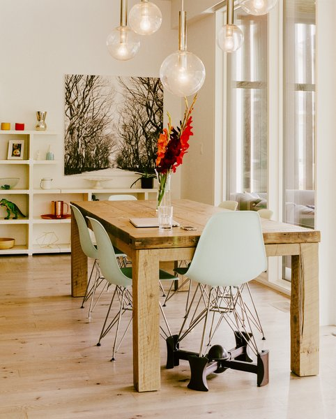 One of the Eames Molded Plastic chairs is lifted on a Kaboost base so that a child can eat at the dining table.