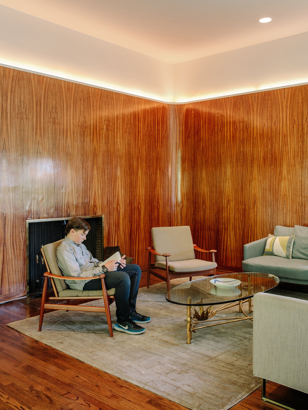 Living Room, Medium Hardwood Floor, Recessed Lighting, Rug Floor, Chair, Standard Layout Fireplace, Sofa, and Coffee Tables In the hearth, more zebrawood paneling is accented by LED strips.  Photo 5 of 15 in Nearly 80 Years Later, an Architect Rescues a Japanese-Inspired  Masterwork Designed by His Father