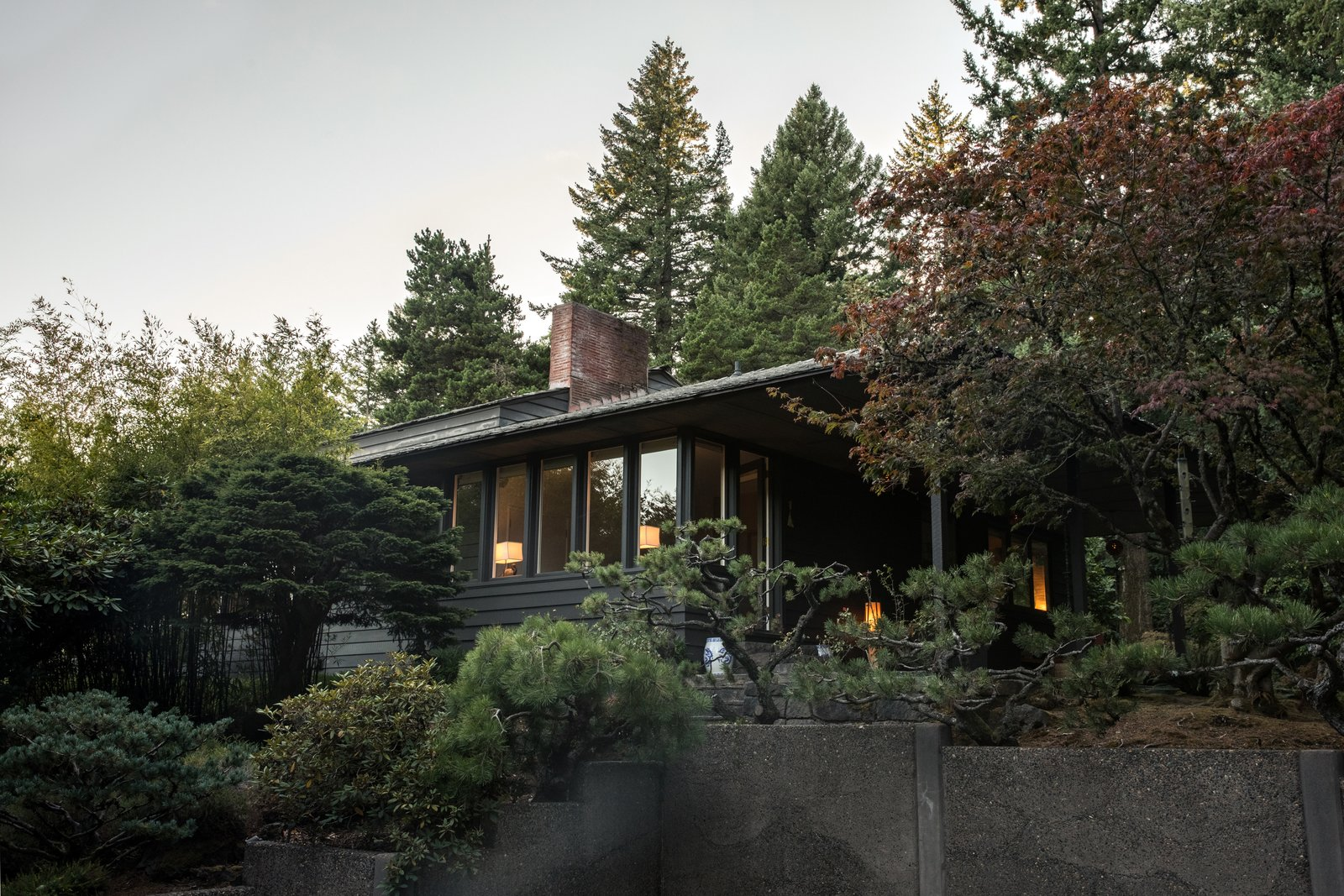 Exterior, House Building Type, Wood Siding Material, and Shingles Roof Material With the aid of landscaper Takashi Fukuda and the home's original plans, the residents are gradually reclaiming the multileveled site.  The 2,300-square-foot home's overhangs shelter its porches (opposite, far right).  Photo 7 of 15 in Nearly 80 Years Later, an Architect Rescues a Japanese-Inspired  Masterwork Designed by His Father