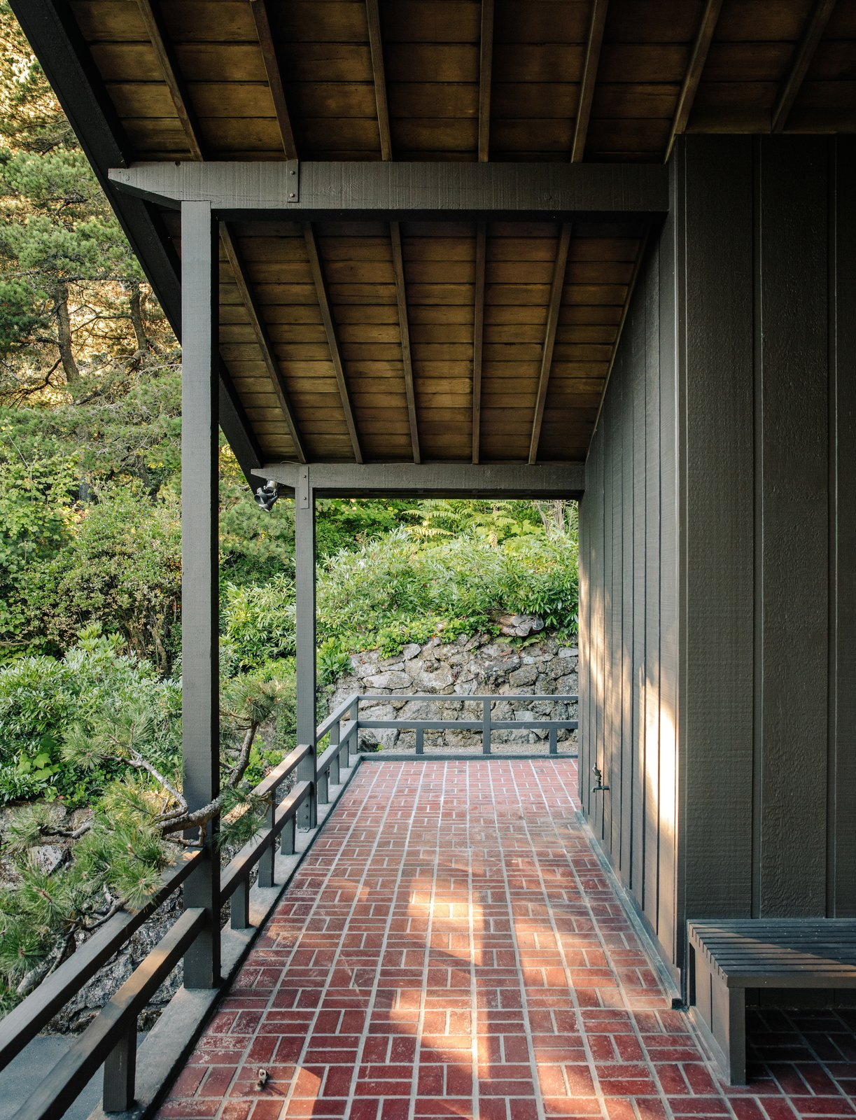 Outdoor, Pavers Patio, Porch, Deck, Stone Patio, Porch, Deck, Trees, Boulders, and Shrubs The 2,300-square-foot home's overhangs shelter its porches.  Photo 10 of 15 in Nearly 80 Years Later, an Architect Rescues a Japanese-Inspired  Masterwork Designed by His Father