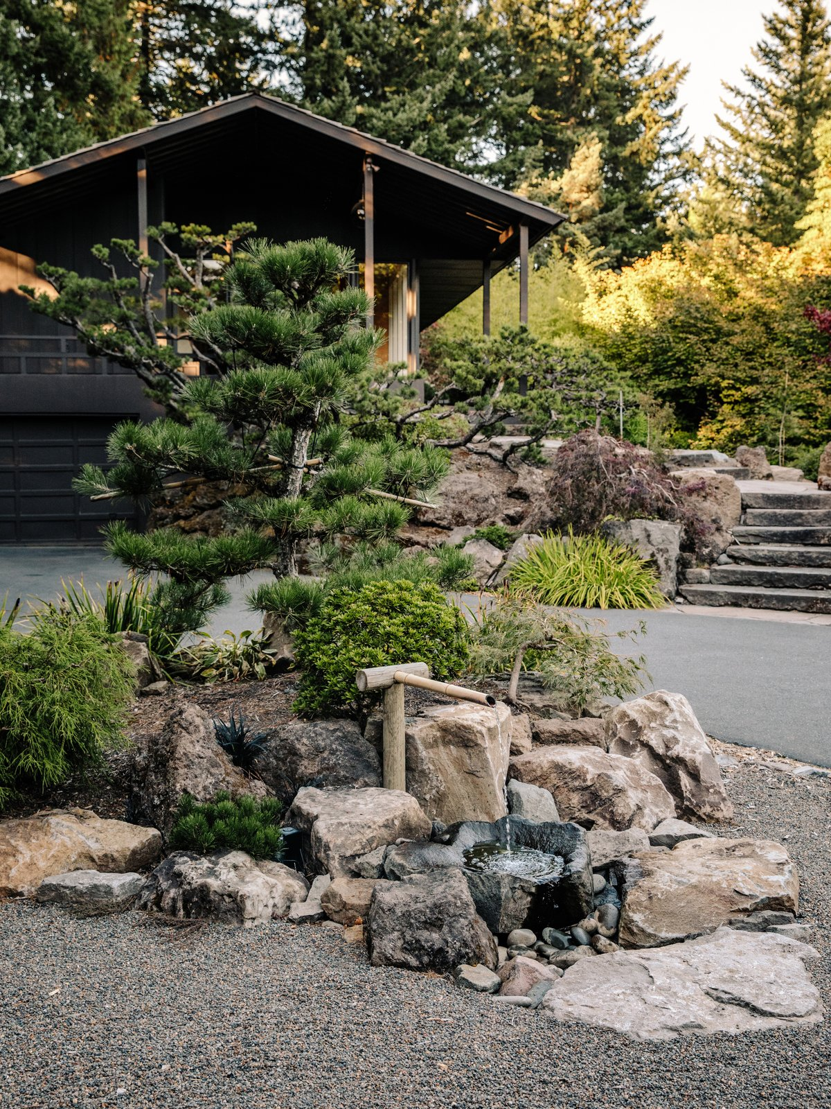 Outdoor, Boulders, Trees, Front Yard, Walkways, Hardscapes, and Garden A Japanese-style Bamboo water fountain sits in the driveway.  Photo 11 of 15 in Nearly 80 Years Later, an Architect Rescues a Japanese-Inspired  Masterwork Designed by His Father