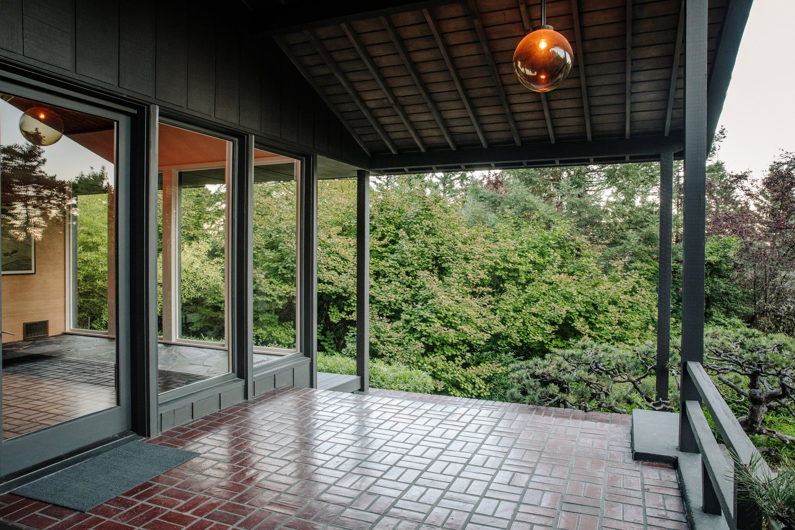 Outdoor, Trees, and Pavers Patio, Porch, Deck The front porch, clad with floor-to-ceiling glass windows, illuminates the foyer inside.  Photo 13 of 15 in Nearly 80 Years Later, an Architect Rescues a Japanese-Inspired  Masterwork Designed by His Father