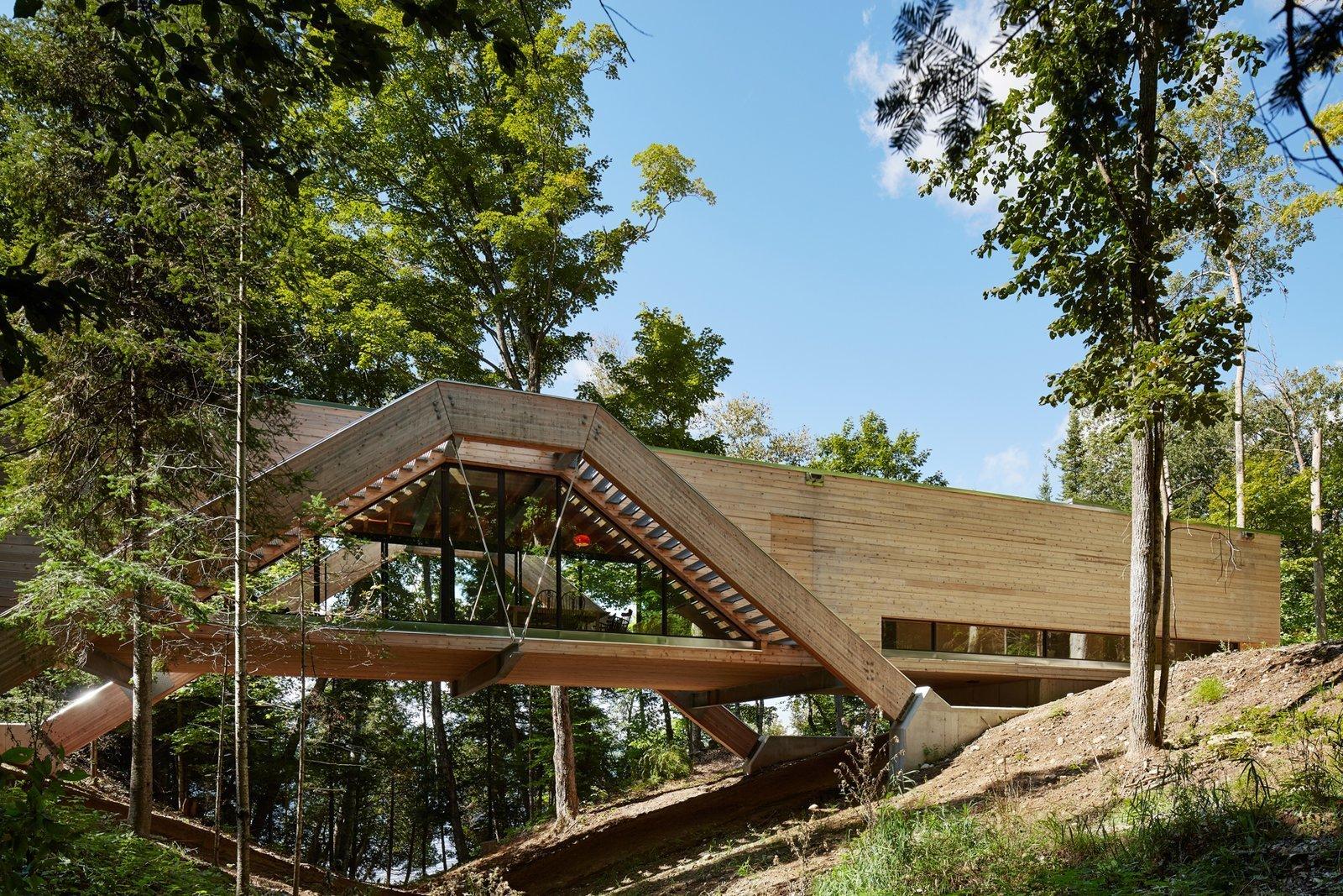 Exterior, Flat RoofLine, Wood Siding Material, and House Building Type  Photo 2 of 12 in A Unique Home in the Canadian Forest That Doubles As a Bridge