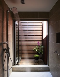 A courtyard off the master bath acts as a solar chimney, drawing in cool air and bringing light and ventilation into the shower. The fixture is from Hansgrohe.