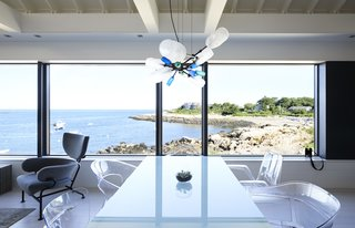 Expanded windows open the first floor to sweeping views of Gap Cove. An assortment of molded acrylic chairs joins a Parsons table from Room & Board.