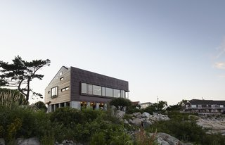 Boulders and native plantings by Ruhl Walker Architects and Annisquam Landcare complement the copper and red cedar cladding.