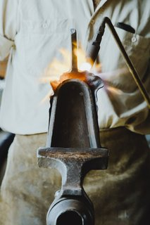 "Shaping the Blade:  A special anvil called a ""stake"" is held in a T-shaped vice. With a torch in his left hand and a hammer in his right, Howard shapes the blade of the shovel around the bell-shaped stake."