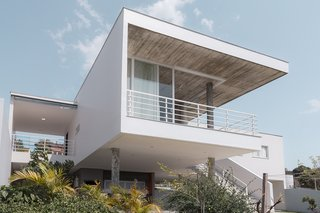 In southern Brazil, a 3,390-square-foot house designed by Barbara Becker and built by Charrua Construções perches on a slope overlooking the city of Pato Branco. The building was constructed out of poured-in-place concrete, which is discretely revealed at specific locations, like the underside of the cantilevered roof and the exposed pilotis at the front of the home. This creates a contrast between the rest of the building's crisp white walls and the rugged texture of the concrete elements.