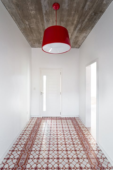 A red Cloche pendant by Newline complements the Fabrica de Mosaicos tile in the entryway. - Pato Branco, Brazil Dwell Magazine : November / December 2017  Photo 3 of 5 in A Brazilian Architect Builds a Dream Home For Her Parents