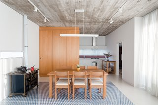 A different pattern by Fabrica de Mosaicos covers the floor in the dining area. Adding texture, the concrete ceiling slab bears the imprint of the wood formwork used to create it. Next to the dining table is an enameled black-and-gold cast-iron Venax stove.