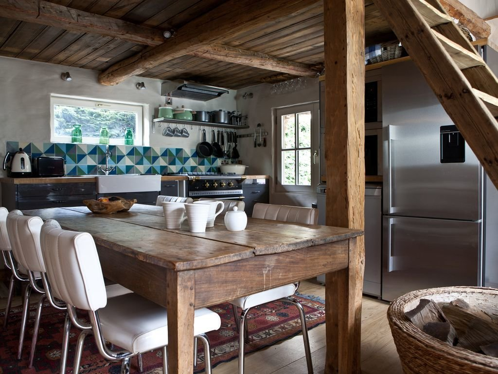 Kitchen, Refrigerator, Wood, Light Hardwood, Ceramic Tile, Ceiling, Wall, Range, Open, Rug, and Vessel  Best Kitchen Ceramic Tile Wall Photos from Rent One of These Cozy Cabins For a Ski Trip This Winter
