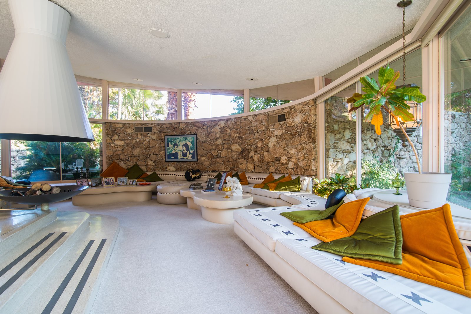 Living Room, Sofa, Sectional, Ottomans, Coffee Tables, Pendant Lighting, Recessed Lighting, Carpet Floor, and Hanging Fireplace  Photo 4 of 8 in Elvis Presley's Palm Springs Honeymoon Retreat Hits the Market