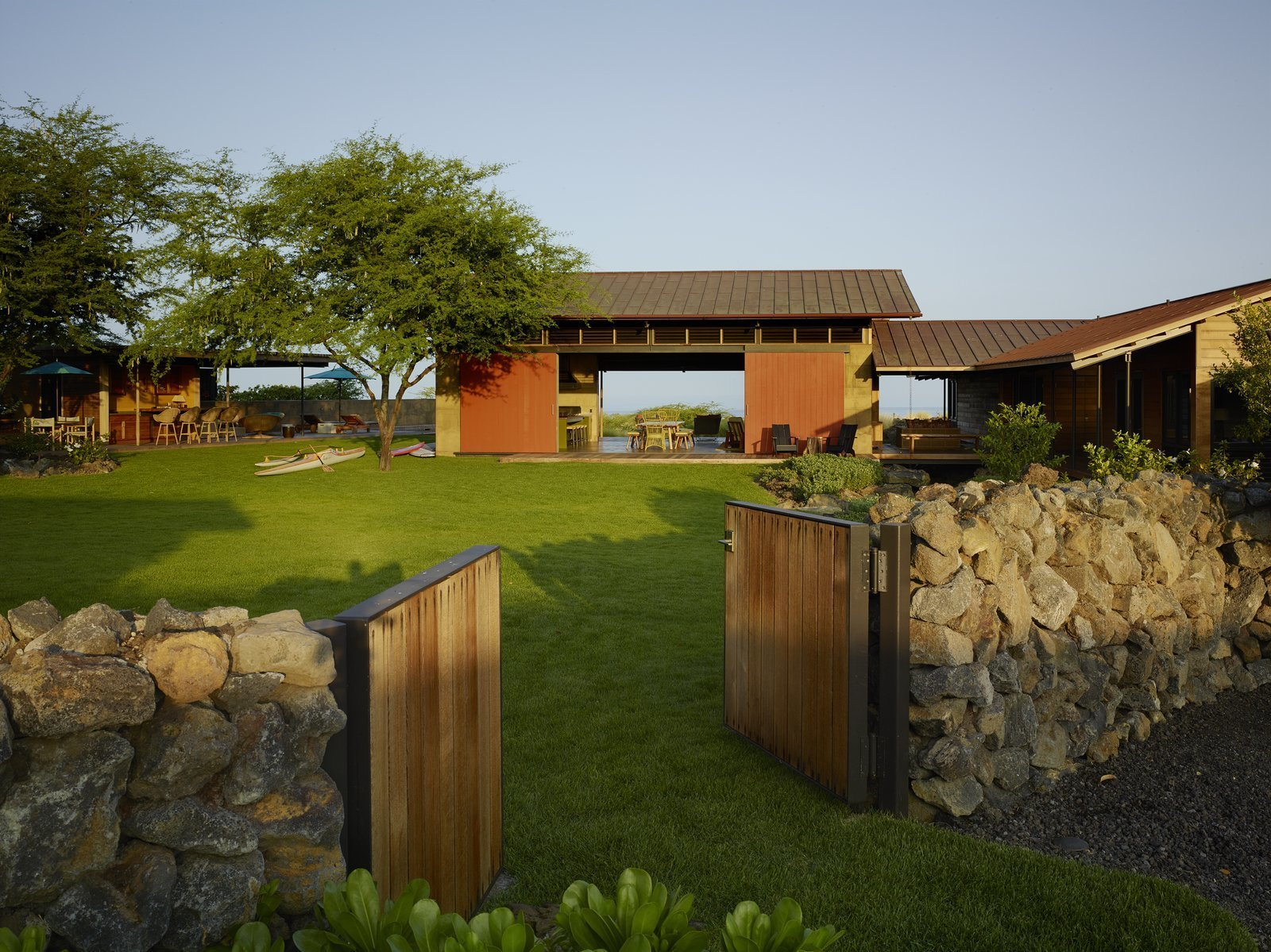 Outdoor, Front Yard, Trees, Grass, Shrubs, Wood Fences, Wall, and Walkways  Photo 1 of 20 in An Incredible Home in Hawaii That's As Much Fun As Summer Camp