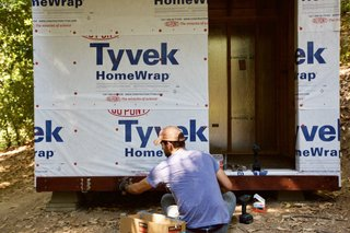You can wrap the whole structure in Tyvek. For The Cube, Waldman used the manufacturer-recommended, plastic-capped nails, but they proved to be a pain. They got in the way of a lot of furring strips and were a problem in the recessed area in front where the siding was attached directly to the sheathing. He ended up pulling a lot of the caps and taping over the nails. He's thinking that he may be able to get away with just staples in the future.