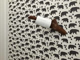 The toilet paper holder is a piece of a madrone tree. Waldman and team installed a bear wallpaper by  Andrea Lauren on Etsy. Make sure to dust and clean the wall extremely well before installing wallpaper, and use one of those $1 plastic scrapers to work the air bubbles out.