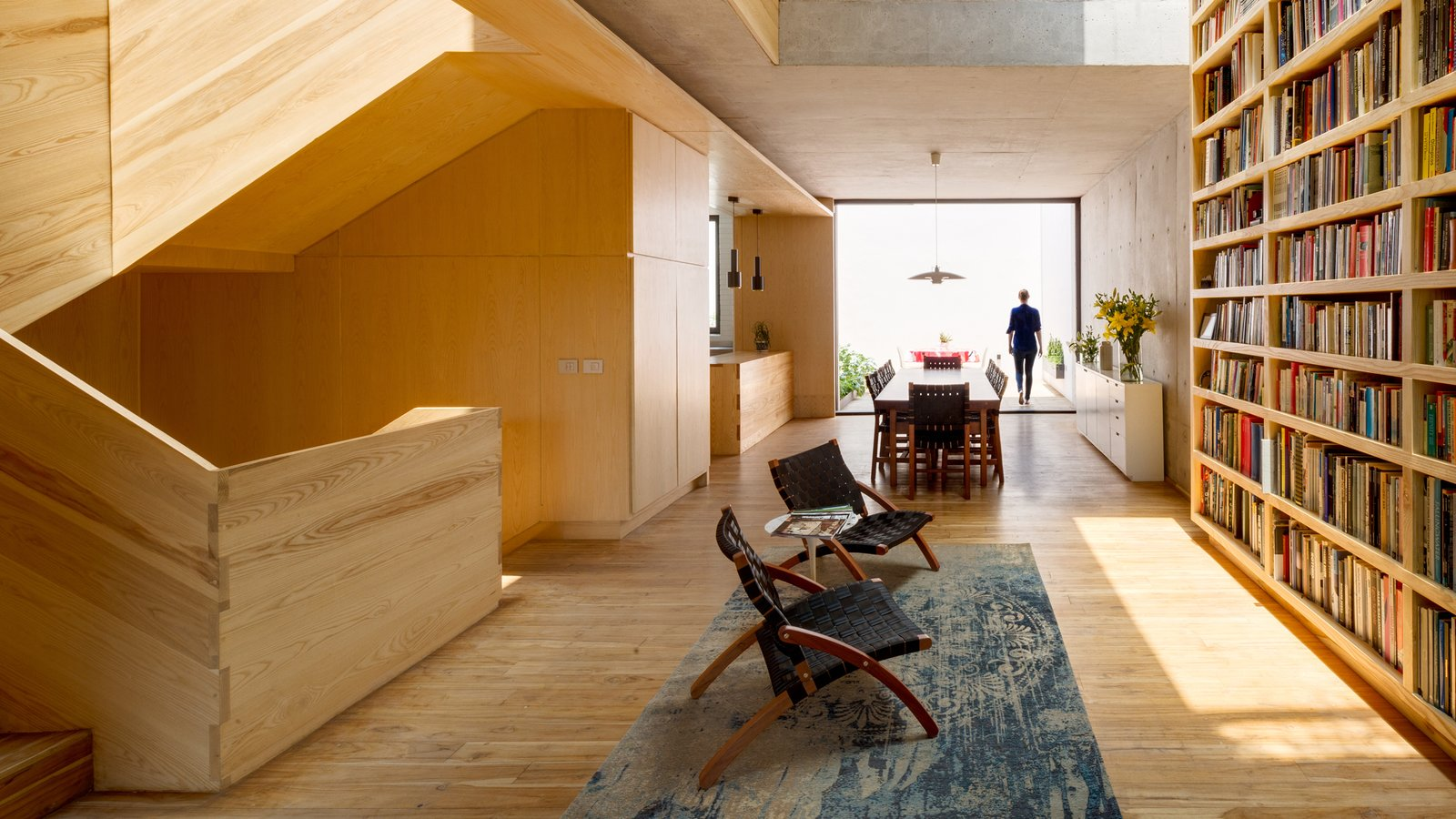Living Room, Rug Floor, Chair, End Tables, Bookcase, and Light Hardwood Floor  Photo 1 of 10 in A Sculptural Wooden Staircase Steals the Show in This Mexico City Abode