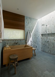 In the master bath, Hale chose slate tile for the floors and green-and-brown glass tile by Lunada Bay for the walls, both from United Tile. The Japanese Ofuro soaking tub, crafted from Hinoki wood, is by Zen Bathworks.