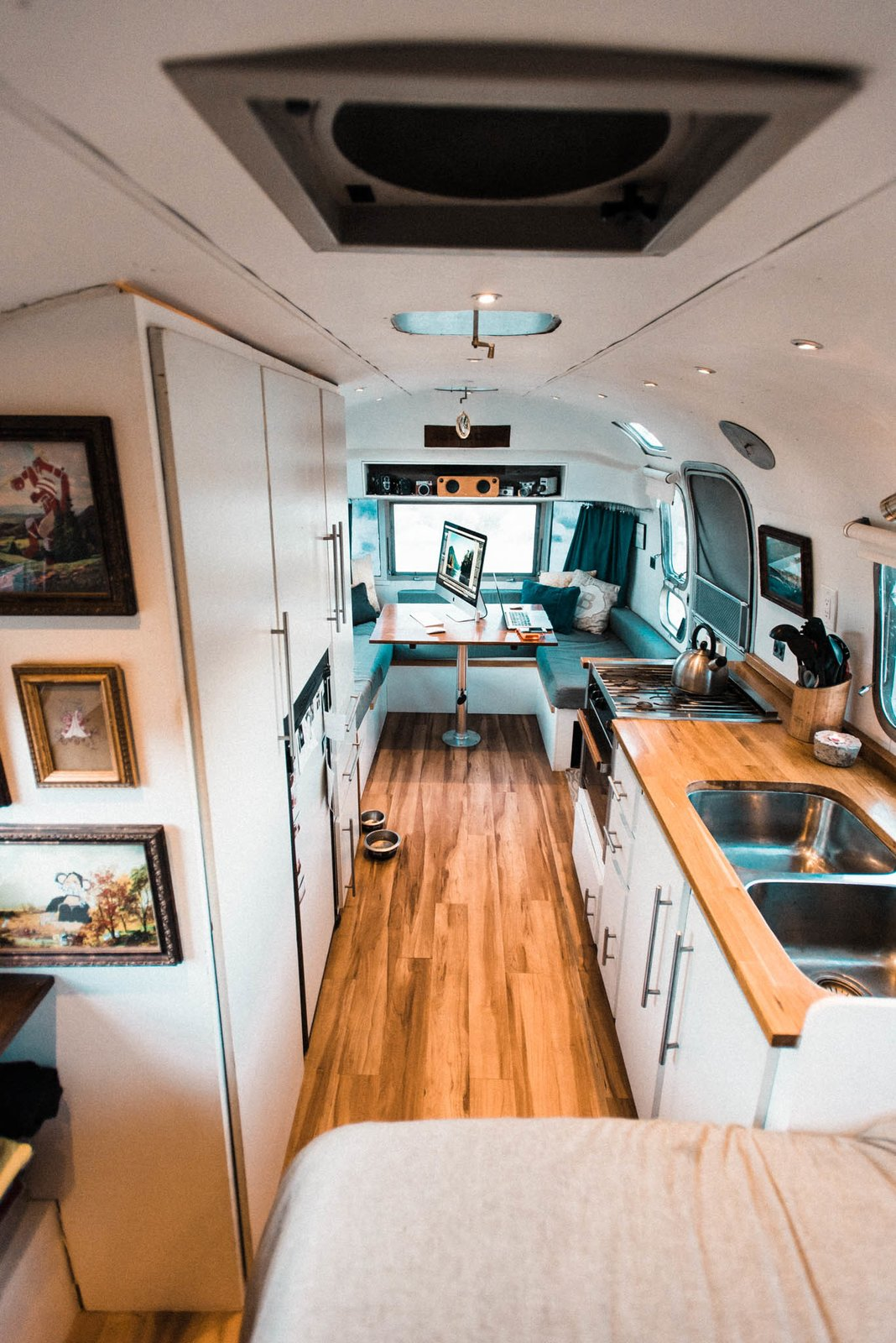 Kitchen, Wood, White, Medium Hardwood, Undermount, Recessed, and Ceiling  Best Kitchen Medium Hardwood Wood Ceiling Photos from A Photographer Couple's Airstream Renovation Lets Them Take Their Business on the Road