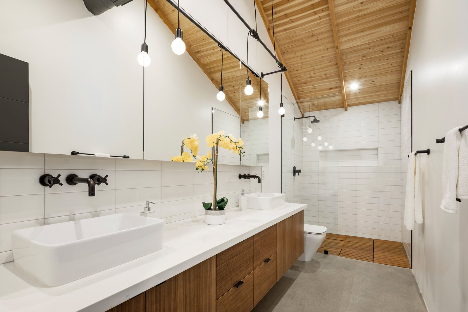 Bath Room, Ceiling Lighting, Vessel Sink, Concrete Floor, Enclosed Shower, Engineered Quartz Counter, Pendant Lighting, One Piece Toilet, and Recessed Lighting  Photo 5 of 13 in In Arizona, a Modern Cube and Tumbledown 1930s Shack Make an Unlikely Couple