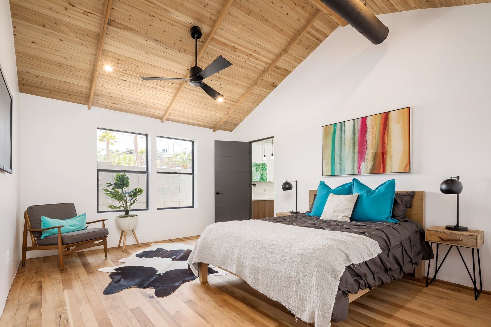 Bedroom, Medium Hardwood Floor, Lamps, Bed, Night Stands, Chair, Ceiling Lighting, and Recessed Lighting  Photo 7 of 13 in In Arizona, a Modern Cube and Tumbledown 1930s Shack Make an Unlikely Couple