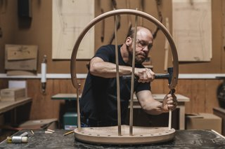 Build: Starting with the longest and shortest lengths, artisan Warren Shaw taps the ash spindles into the top of the seat and the continuous arm with a mallet. The legs will follow.