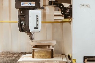 Shape the Seat: In a nine-minute automated process, a CNC machine routs and shapes the panel into an ergonomically correct seat. It also drills holes for the spindles and legs. By hand, this step alone would take hours.