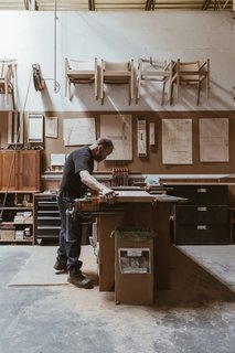 "At the workshop in Auburn, Maine, master craftsman Warren Shaw glues and clamps together three pieces of cherry to make a panel that will form the seat of a Continuous Arm Chair. The artisans sometimes call the piece ""TMC""­—Thos. Moser Continuous—for short."