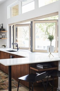 A 14-foot-wide opening defines the kitchen, which architect Scott Delano, with Nicholas Pettit, carved out of what had been an enclosed breezeway and part of the garage. The bifold window is from NanaWall, the windows above are by Pella, and <br>the faucet is by Blanco.