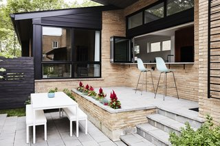 Midcentury Mashup: A 1950s Ranch House in Chicago Gets a Palm Springs-Style Butterfly Roof - Photo 5 of 15 - In the front courtyard, a raised bluestone patio was built off the new kitchen for casual meals and entertaining. The Eames Molded Plastic Chairs are from Herman Miller. The dining table and benches are from Room & Board.